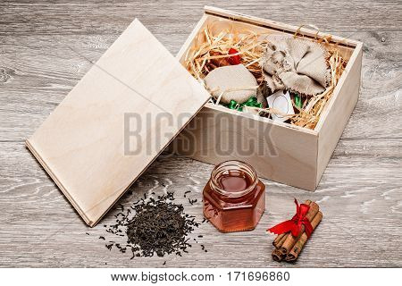 Honey, cinnamon, tea leaves, wooden box on a light wooden background
