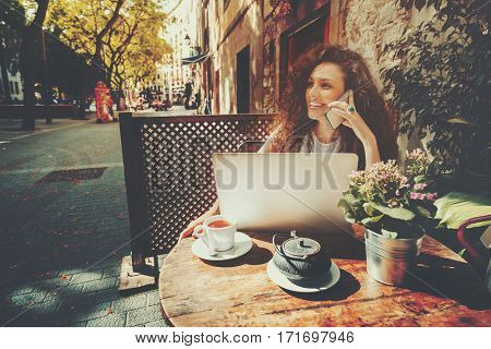 Young curly woman calling with cell telephone while sitting alone in street cafe during free time attractive brunette laughing girl having talking on smartphone while work on her modern laptop