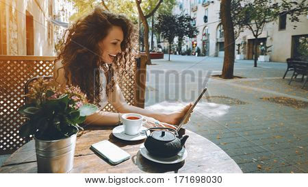 Young curly woman talking in video chat with her friend via digital tablet while sitting in street cafe and drink delicious black tea laughing girl watching comedy movie on touch pad during breakfast
