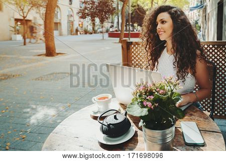 Cute beautiful caucasian freelancer girl with curly black hair is sitting in street cafe with cup and teapot of delicious black tea in front of wooden fence and working on her laptop on sunny day