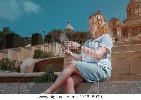 Plus size girl is watching drama movie on her digital tablet while sitting on stairs in sunny day blonde girl in white t-shirt and grey skirt is having video chat via touch pad with her family