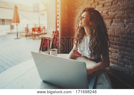 Brunette cheerful woman freelancer in good mood using laptop computer for distance work during drinking tea in cafe attractive girl with black curly hair sitting with portable net-book in street bar