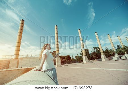 Blond plus size girl in white t-shirt and grey skirt is texting message to her friend while standing on the square on sunny day with copy space for your advertising text message or promotional content