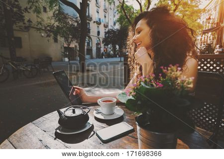 Young curly woman talking in video chat with her family via digital tablet while sitting in street cafe and drink delicious black tea smiling girl watching drama movie on touch pad during breakfast