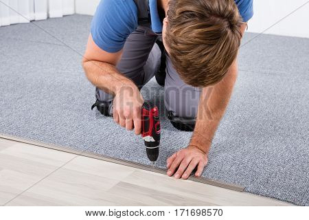 Close-up Of Carpenter Using Wireless Screwdriver For Fixing Carpet