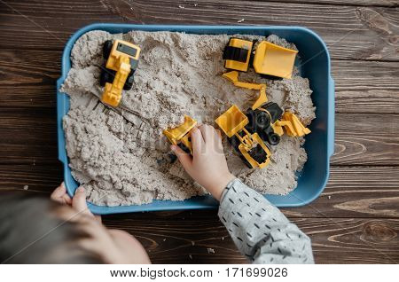 Child Playing With Kinetic Sand And Toy Construction Machinery