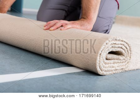 Close-up Of Worker's Hands Rolling Carpet At Home