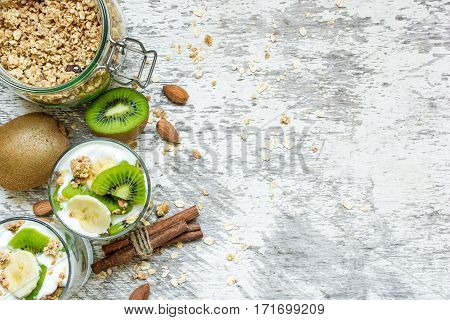 Homemade yogurt parfait with granola kiwi fruit banana and nuts in a glasses for healthy breakfast on rustic wooden background. top view