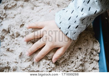 Child Playing With Kinetic Sand.