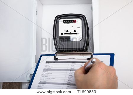 Close-up Of A Technician Hand Writing Reading Of Meter On Clipboard