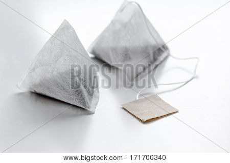Two pyramid teabags of black tea on white table background mock-up