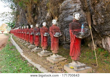 Buddhist monks stone statues row at Ka Thawng cave, Hpa-an, Myanmar