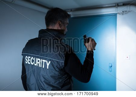 Rear View Of A Male Security Guard With Flashlight Standing In Front Of Door