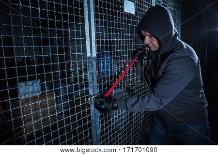 Burglar Trying To Break The Gate Of Storage Room With A Crowbar