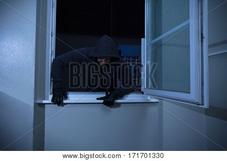 Burglar Entering In Room Through The Window At Nighttime