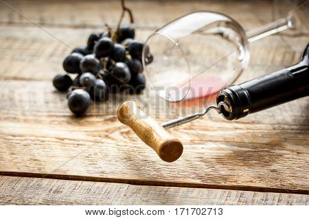 restaurant set with red wine bottle, glass and fresh grape on wooden table background