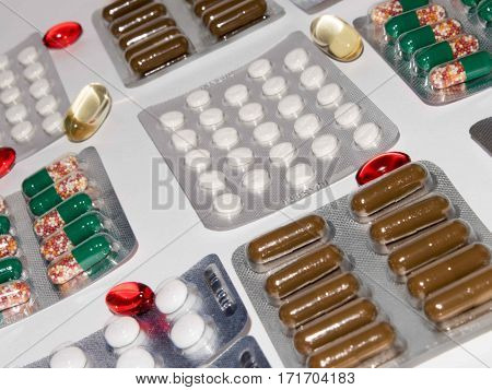 Tabs Vitamins omega 3 Medications tablets and capsules in a beaker. Medications tablets suppository bottles capsules and thermometer on wooden table