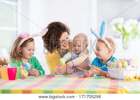 Mother With Three Children Painting Easter Eggs