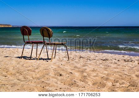 Two old chairs on the beach. Two is always better than one. Together, even in old age better. The invitation to sit and think about the past.