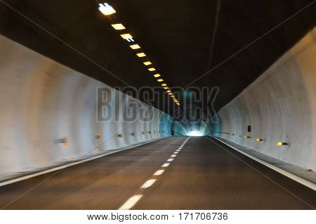 Road tunnel in the mountains. Bright white light at the end of the tunnel. Association of life and death hope mystery the beginning or the end of something.