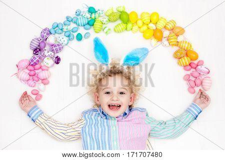 Child On Easter Egg Hunt. Pastel Rainbow Eggs.