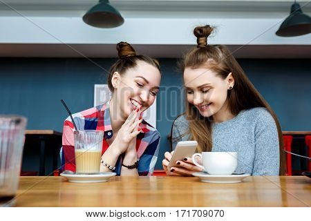 two young beautiful hipster women sitting at cafe, talking, flirty, stylish trendy outfit, europe vacation, street style, happy, having fun, smiling, sunglasses, positive mood