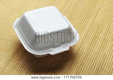 Styrofoam Takeaway Food Box on Bamboo Mat Background