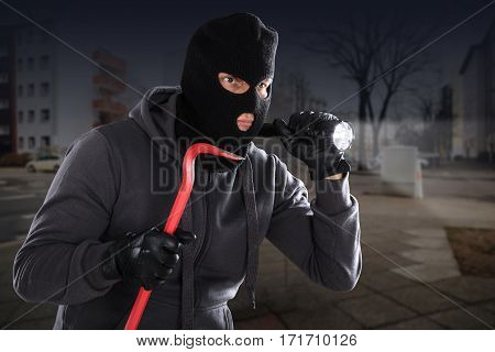 Burglar With A Crowbar And A Flashlight Standing On A Roadside