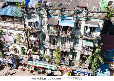 Yangon Myanmar - 2017 January 7 : A historic colonial residential building in downtown Yangon seen from above with balconies and shops in the street below Burma