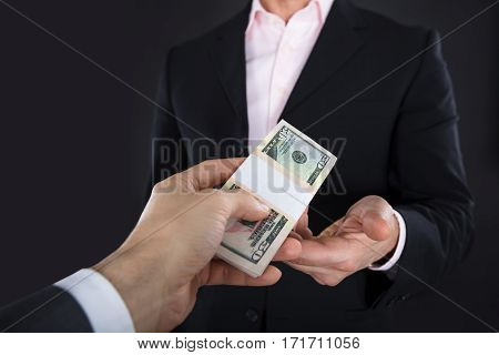Close-up Of A Businessman Receiving A Bank Note On Black Background