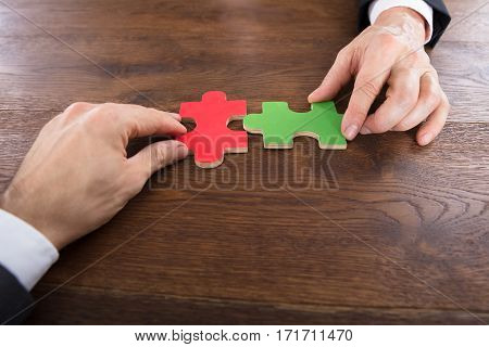 Close-up Of Two Businessmen Joining Jigsaw Pieces On Wooden Desk