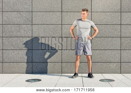 Full length of determined jogger standing against tiled wall outdoors