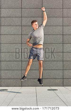 Full length of excited runner jumping against tiled wall