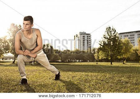 Full length of confident young man exercising in park