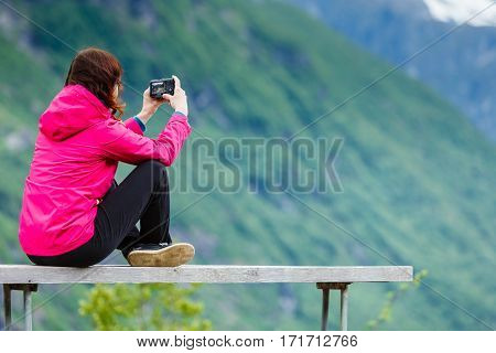 Tourism adventure and travel. Female tourist hiker sitting on bench in stone mountains taking photo with camera looking at scenic view Norway Scandinavia. poster
