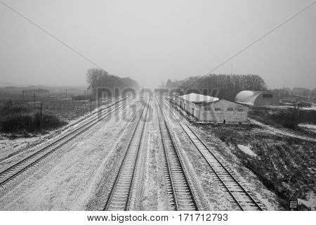 Belarus - November 2016 Long railroad tracks in the snow winter on the railroad farm sheds endless path top view view from the bridge fog black and white imageroad sign