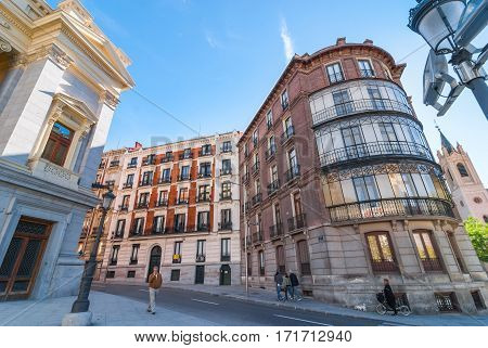 Editorial:   Madrid, Spain, November 9th, 2013:   Living in Spain.  People walk by Roman style Prado Museum.  Woman on her bicycle, small, 5 storey condo buildings within walking distance of a historical archive.