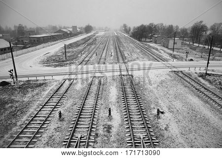 Belarus - November 2016 Long railroad tracks in the snow winter on the railroad farm sheds endless path top view view from the bridgerailway traffic black and white imageroad sign