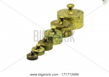 A collection of antique brass calibration weights isolated on white.