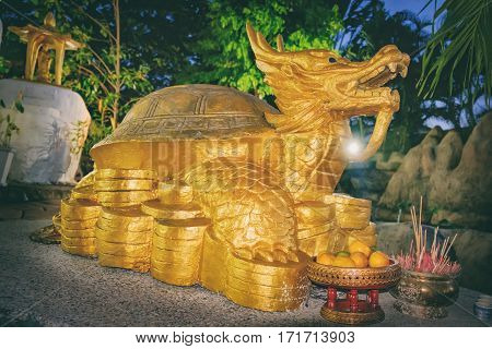 Khao Lak, Thailand - December 28, 2015: Dragon with turtle shell - symbol of prosperity and success in China. Golden statue near small Chinese temple at night, Nang Thong Beach, Khao Lak, Thailand