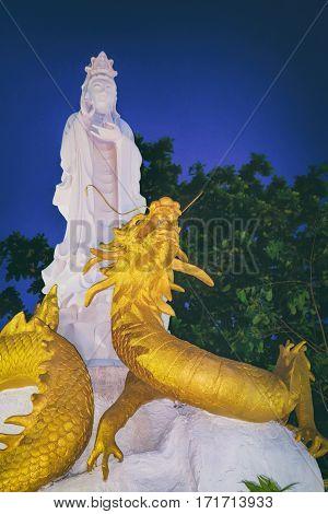Khao Lak, Thailand - December 28, 2015: White Guan Yin Buddha and the Chinese Golden Dragon Statue near small Chinese temple at night Nang Thong Beach, Khao Lak, Thailand