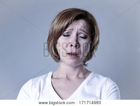 close up portrait of young beautiful woman on her 30s sad and depressed looking low and tormented feeling worried suffering breakdown isolated background in depression emotion crying