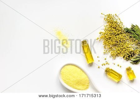 Yellow cosmetic sea salt with essential oils on white background top view mock up