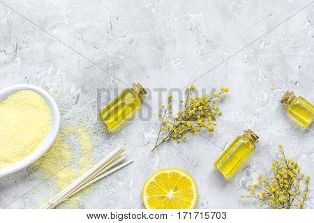 Cosmetic aroma oil and sea salt for bath on gray background top view mock-up