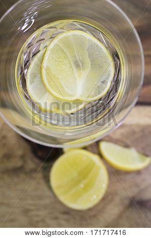 Lemon liqueur with lemon wedges served in a crystal stem glass