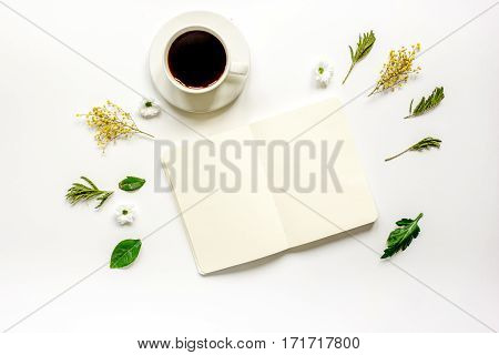 Floral flat lay with cup of coffee and opened copybook on white background top view mock up