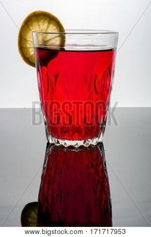 A Glass With Red Drink On A Light Background.