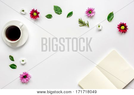 Flower petals, cup of coffee and white copybook on table background top view mock up