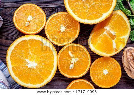 fresh orange juice squeezing on dark wooden kitchen table background top view