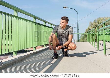 Full length of male jogger tying shoelace on bridge